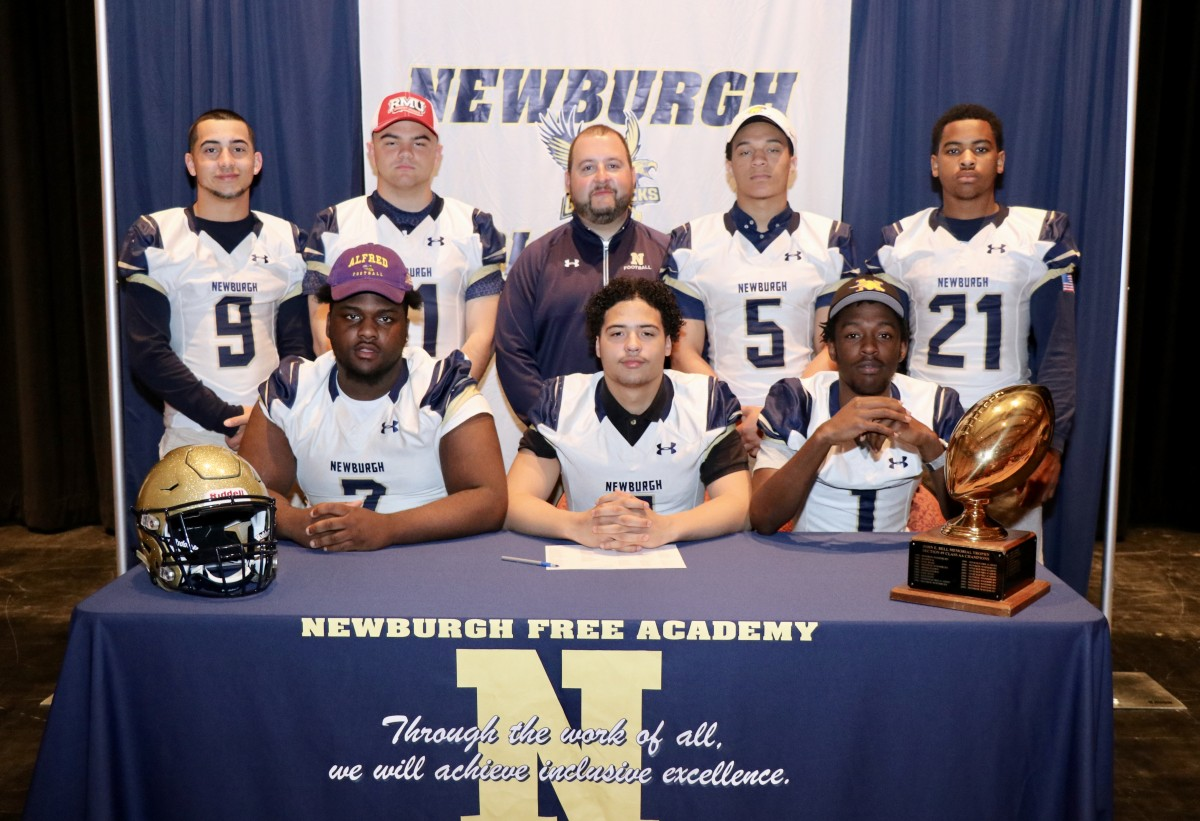Eight students who signed to play football in college with their coach.