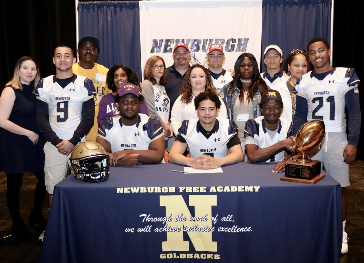 Eight students who signed to play football in college with their family.