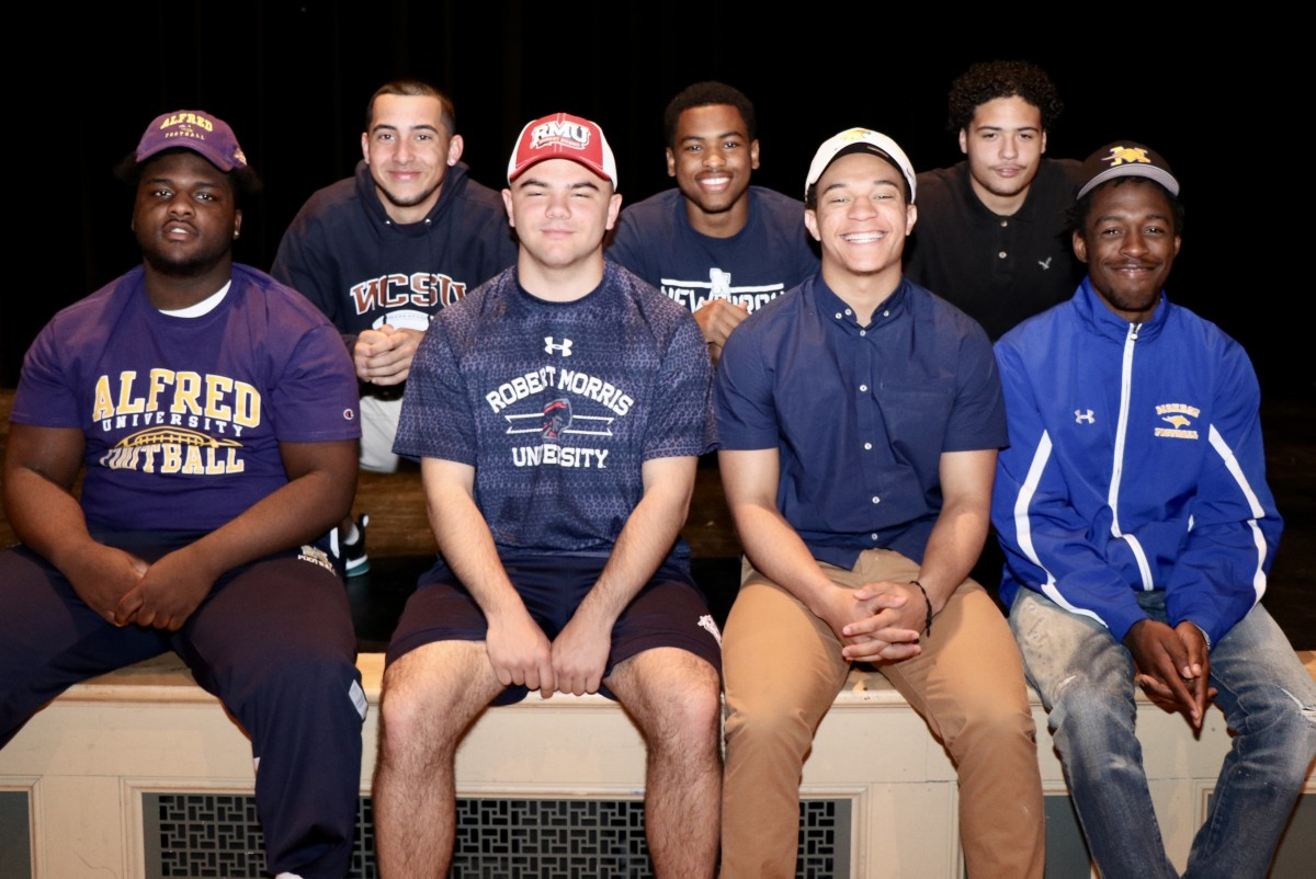 Eight students who signed to play football in college in their college gear.