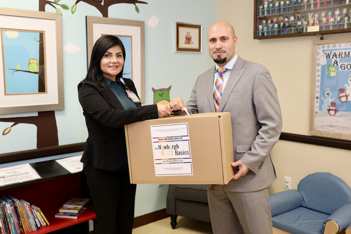Dr. Padilla hands Basics kit to Cornerstone Family Health