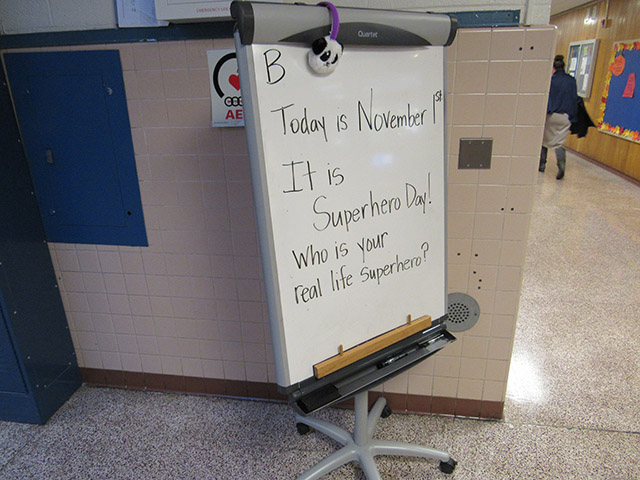 Dry Erase Board about Super Hero day in the front lobby