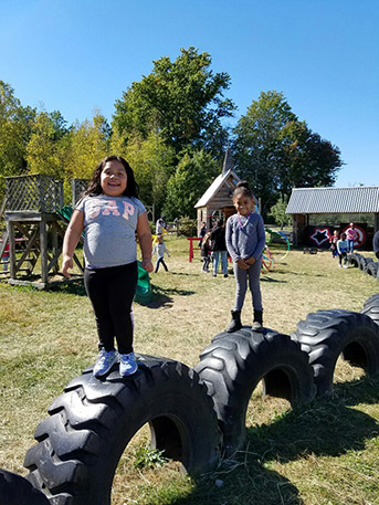 Other students playing on farm playground.