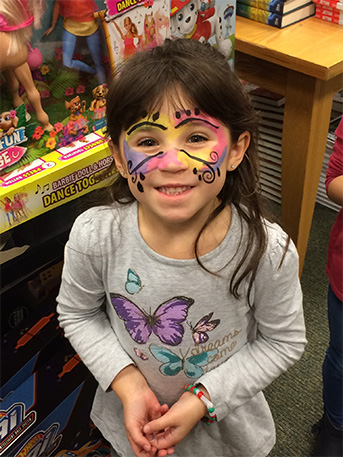 A student has her face painted at the event