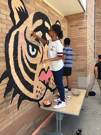 A student painting the lion mural