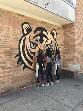 Another photo of students working on mural