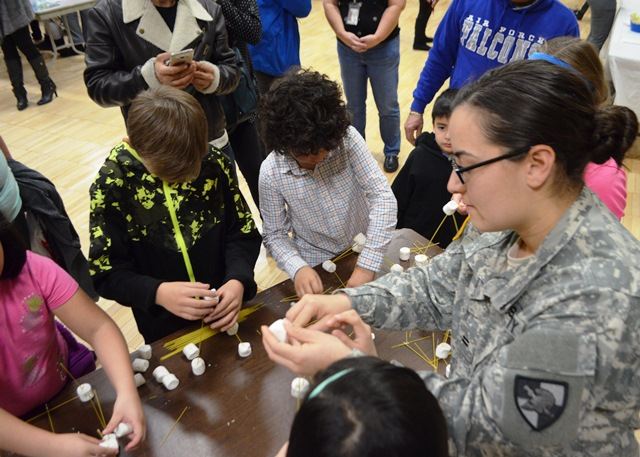 A Cadet works with students on projects