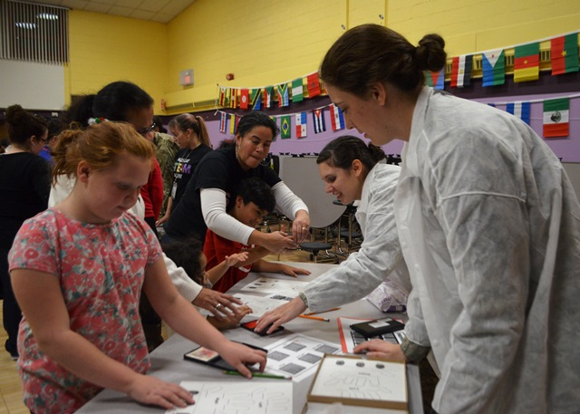 Students work with cadets on a project