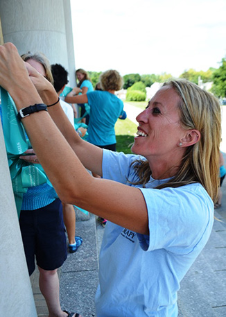 A teacher places a teal ribbon on a column