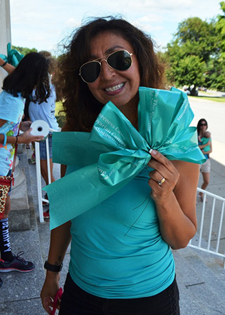 A teacher holding a teal ribbon