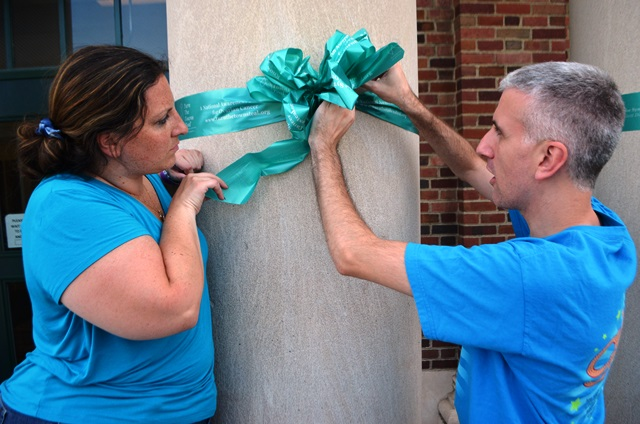 Two teachers working together to tie a ribbon