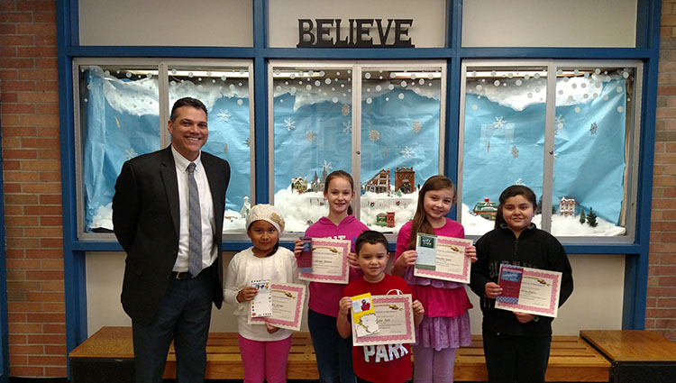 Winners of the Temple Hill Academy December essay contest, Traditions, pose with their principal, Mr. Lopez.